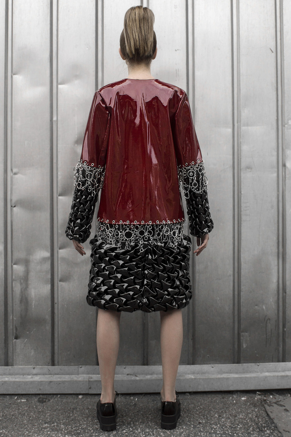 Look 2   Lacquered leather coat with raw metal embellishments and hand-smocked  3-D fabric.