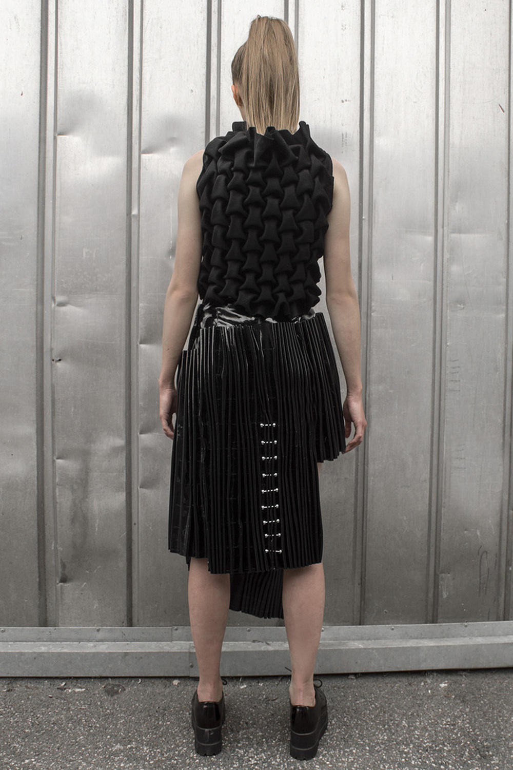 Look 6  Hand-smocked cashmere top with metal embellishments and a pleated, black vinyl skirt